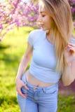 Recht blonde weibliche Person, die im Park ith Blütenhintergrund steht Stockbild