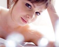 Recht blonde wirkliche Frau, die in Bett legt Lizenzfreies Stockfoto