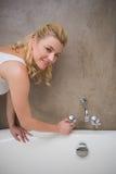Recht blonder Betrieb ein Bad, das an der Kamera lächelt Stockfotos