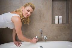 Recht blonder Betrieb ein Bad, das an der Kamera lächelt Lizenzfreie Stockbilder