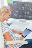 Recht blonder Bildeditor, der an einem Tablettencomputer arbeitet Lizenzfreies Stockfoto