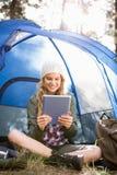 Recht blonder Camper, der Tablette verwendet und im Zelt sitzt Lizenzfreie Stockbilder
