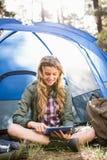Recht blonder Camper, der Tablette verwendet und im Zelt sitzt Lizenzfreies Stockfoto