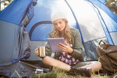 Recht blonder Camper, der Tablette verwendet und Schale hält Lizenzfreies Stockbild