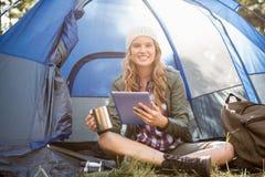 Recht blonder Camper, der Tablette verwendet und Schale hält Stockfotografie