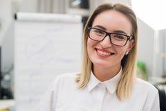 Recht blonder Designer, der an der Kamera im kreativen Büro lächelt Lizenzfreie Stockfotografie