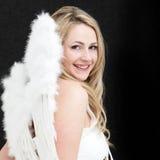 Recht blonder Engel mit einem hellen Lächeln Stockfotografie
