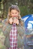 Recht blonder Lagerbewohner, der Getränk vor Zelt genießt Stockbild