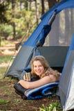Recht blonder Lagerbewohner, der im Zelt lächelt und liegt Lizenzfreie Stockbilder
