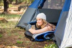 Recht blonder Lagerbewohner, der im Zelt lächelt und liegt Stockbild