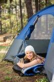 Recht blonder Lagerbewohner, der im Zelt lächelt und liegt Lizenzfreies Stockfoto