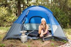 Recht blonder Lagerbewohner, der im Zelt lächelt und sitzt Stockfotografie