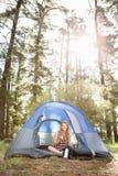 Recht blonder Lagerbewohner, der im Zelt lächelt und sitzt Stockfoto