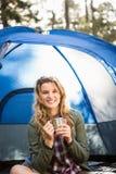 Recht blonder Lagerbewohner, der im Zelt lächelt und sitzt Stockbilder