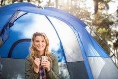 Recht blonder Lagerbewohner, der im Zelt lächelt und sitzt Lizenzfreie Stockfotos
