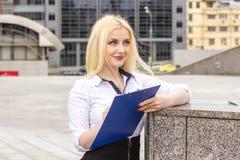 Recht blonder Manager mit Dokumenten draußen Stockfotografie
