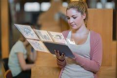 Recht blonder Student, der an ihrer digitalen Tablette arbeitet Lizenzfreie Stockbilder