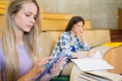 Recht blonder Student, der Tablette verwendet Stockfoto