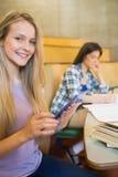 Recht blonder Student, der Tablette verwendet Stockbilder