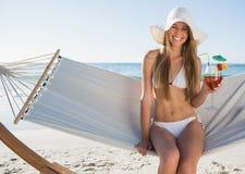 Recht blonder tragender Bikini und sunhat, die auf Hängematte mit sitzt Stockbild
