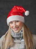 Recht blonder tragender Weihnachtshut auf Dunkelheit Stockfotografie