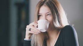 Recht blonder trinkender Kaffee der jungen Frau und Lächeln im Café Stockfoto