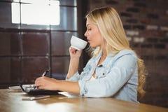 Recht blonder trinkender Kaffee und Schreiben in Planer Stockfotos