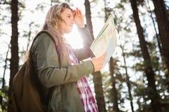 Recht blonder Wanderer mit der Karte, die nach Weg sucht Stockfoto