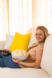 Recht blondes aufpassendes Fernseh- und essenpopcorn Lizenzfreies Stockbild