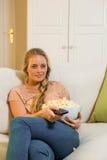 Recht blondes aufpassendes Fernseh- und essenpopcorn Stockbild