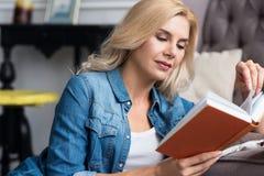 Recht blondes Damenlesebuch Lizenzfreies Stockfoto
