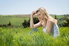 Recht blondes Denken beim Sitzen auf Gras Stockfoto
