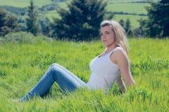 Recht blondes Denken beim Sitzen auf Gras Stockfotos