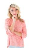 Recht blondes Denken mit der Hand auf Kinn Stockbilder