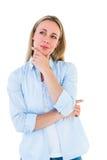 Recht blondes Denken mit der Hand auf Kinn Lizenzfreie Stockfotografie