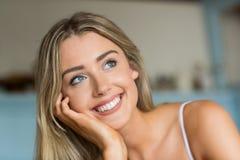 Recht blondes Denken und Lächeln Lizenzfreie Stockfotografie