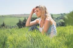 Recht blondes Denken und Sitzen auf Gras Lizenzfreies Stockbild