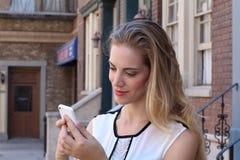 Recht blondes draußen simsen auf städtischem Hintergrund Lizenzfreie Stockfotografie
