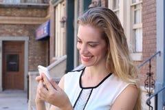 Recht blondes draußen simsen auf städtischem Hintergrund beim Lächeln Stockbild