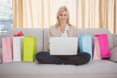 Recht blondes Einkaufen online mit Laptop Lizenzfreie Stockfotos