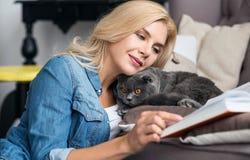 Recht blondes Frauenlesebuch mit ihrer Katze Lizenzfreie Stockbilder