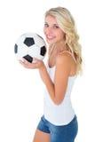 Recht blondes Fußballfan, das Ball hält Lizenzfreies Stockfoto