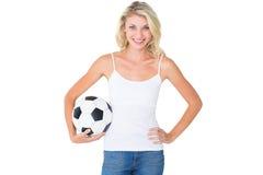Recht blondes Fußballfan, das Ball hält Lizenzfreies Stockbild