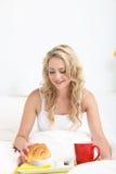 Recht blondes genießendes Frühstück im Bett Stockfotografie
