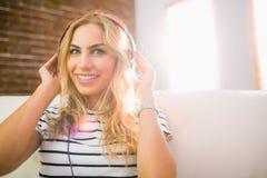 Recht blondes Hören Musik auf Couch Lizenzfreies Stockfoto