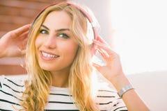 Recht blondes Hören Musik auf Couch Stockfoto