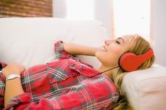 Recht blondes Hören Musik auf Couch Lizenzfreie Stockfotos