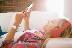 Recht blondes Hören Musik auf Couch Lizenzfreies Stockbild