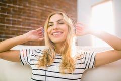Recht blondes Hören Musik auf Couch Lizenzfreie Stockfotografie