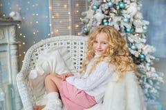 Recht blondes kleines Mädchen sitzt auf einem Stuhl nahe einem Kamin und einem Weihnachtsbaum Lizenzfreie Stockbilder